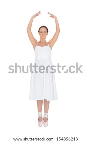 Focused young ballet dancer standing on her tiptoes on white background  - stock photo