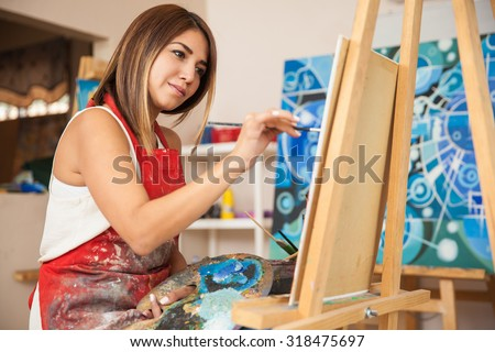 Focused young female artist working on a new painting in her workshop - stock photo