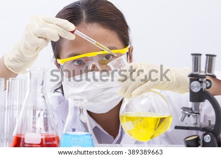 Focused young life science professional pipetting solution into the glass cuvette. Lens focus on the researcher's eye. - stock photo
