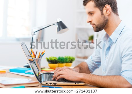 Focusing at work. Handsome young man in shirt working on laptop while sitting at his working place - stock photo