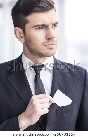 Focusing businessman is looking away and puts in his pocket business card. - stock photo