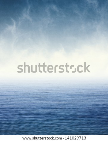 Fog and clouds hovering over the Pacific ocean.  Image displays a pleasing paper grain and texture at 100%. - stock photo