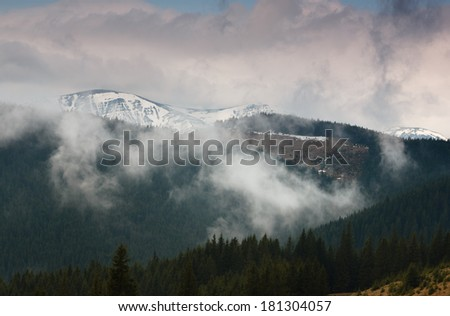 Fog and clouds over mountain forests and snow slopes  - stock photo