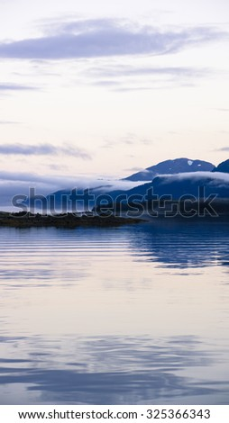 Fog and low clouds near Sullivan Island in Southeast Alaska at sunset. - stock photo