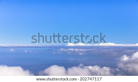 Fog bank between blue sky and ocean. - stock photo