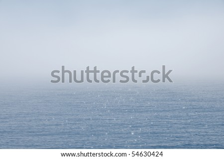 Fog in the middle of the blue ocean and some sparkling reflections shining through  it. - stock photo