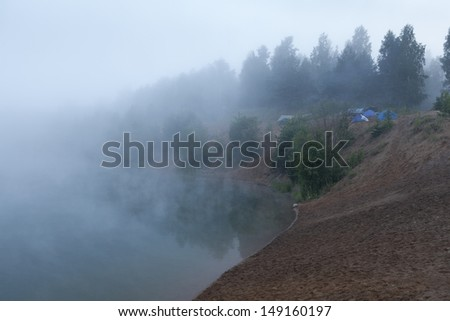 Fog on the lake with standing tourist tents at early morning - stock photo
