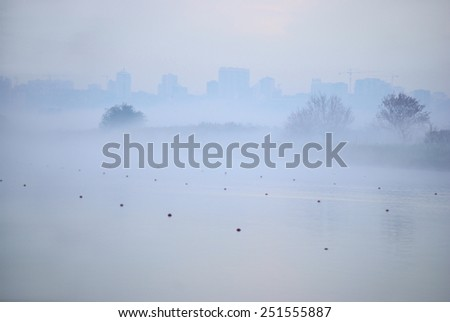 Fog over the river. City on the background. - stock photo