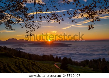 Fog surrounding town Zug and Zugersee during the sunset with the Pilatus and Swiss Alps in the background - stock photo
