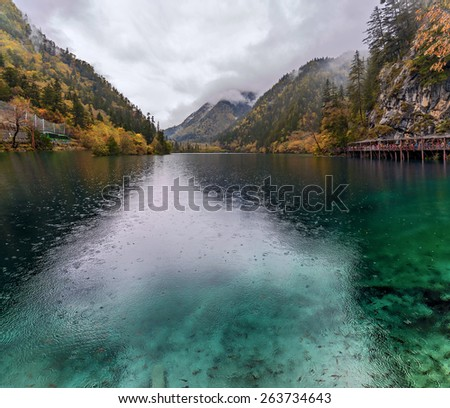 Foggy lake with submerged tree trunks in the rain. Jiuzhaigou Valley was recognize by UNESCO as a World Heritage Site and a World Biosphere Reserve - China - stock photo