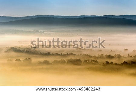 Foggy landscape summer river valley. The first rays of the rising sun. - stock photo