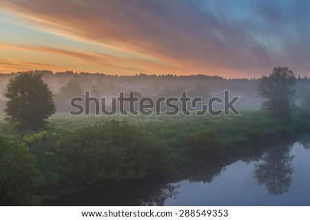 Foggy morning in the village at the river. Sunrise on the river bank in the village. Bright fine sunrise. Dawn bright clouds over the village at the river. Early twilight outdoors. Sunrise in Russia - stock photo