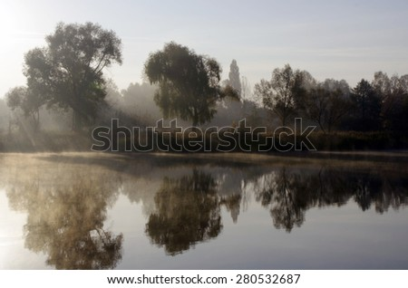 Foggy morning landscape blur in the autumn park near the lake. - stock photo