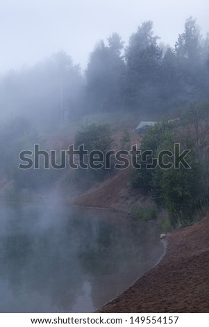 Foggy morning on forest lake with standing tourist tents on bank - stock photo