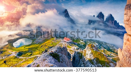 Foggy morning scene in the National Park Tre Cime di Lavaredo with rifugio Lacatelli and Del Piani Lakes. Sunrise in Dolomite Alps, South Tyrol. Location Auronzo, Italy, Europe. - stock photo