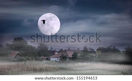 Foggy night and moonrise over farmland - stock photo