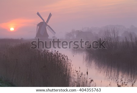 Foggy, pink sunrise in Holland with a traditional windmill in the wetlands. - stock photo