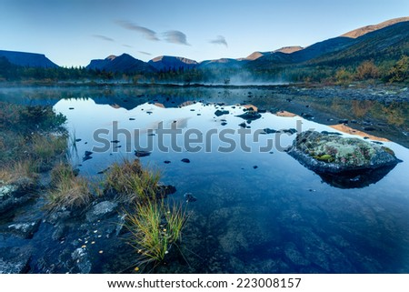Foggy Polygonal freshwater lake with rocks and tussock in the foreground in Hibiny mountains in the early morning before sunrise - stock photo