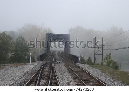 Foggy railroad bridge - stock photo