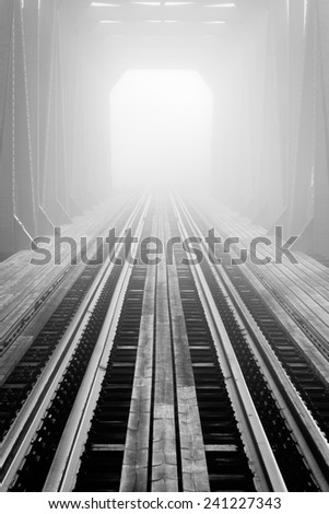 Foggy railway bridge - stock photo