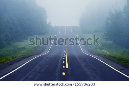 Foggy Road Ahead. Road Through Minnesota Wilderness.  - stock photo