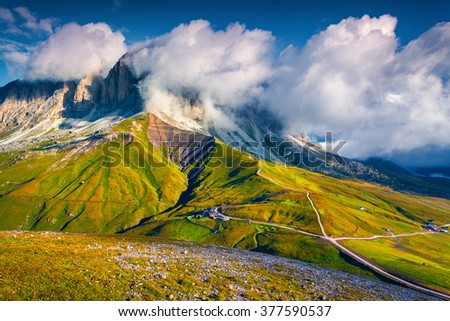 Foggy summer scene on the Sassolungo (Langkofel) group. View from the Sella pass. Sunny morning in Dolomite Alps, Province of Bolzano - South Tyrol, Italy, Europe. - stock photo