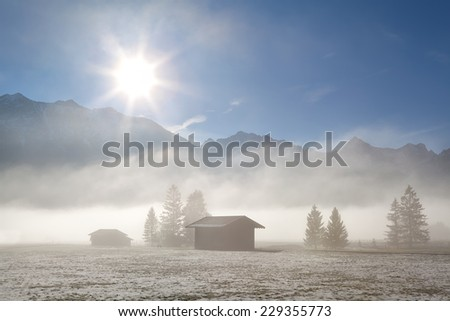 foggy sunny morning over winter alpine meadows, Germany - stock photo