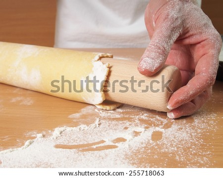 Fold edge of pastry round over rolling pin. Making Apple Pie Tart Series. Wrap pastry around rolling pin. - stock photo