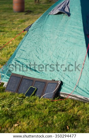 Foldable solar panel charges mobile phone on mountain base camp - stock photo