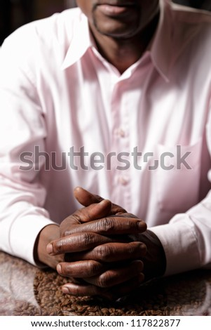 Folded hands of a guy in pink shirt - stock photo