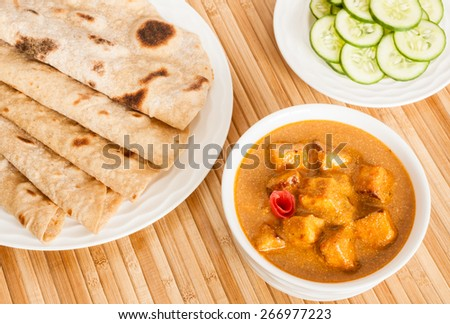 Folded homemade wheat chapati (Indian bread) served with delicious Indian paneer butter masala and cucumber salad. It is prepared using paneer (cottage cheese), butter, tomato and various spices. - stock photo