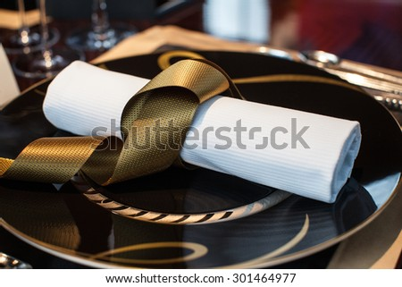 folded napkin laid on plate on the table at restaurant - stock photo