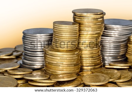 Folded stack of coins of yellow and white metal - stock photo