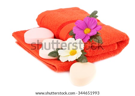 Folded towel, soaps and flower isolated on white background. - stock photo