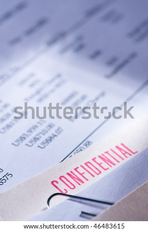 "Folder labeled ""confidential"" on top of some business documents. - stock photo"