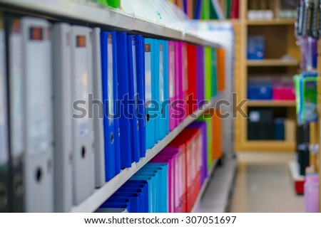 Folders for documents and goods and products on shelves in stationery shop - stock photo