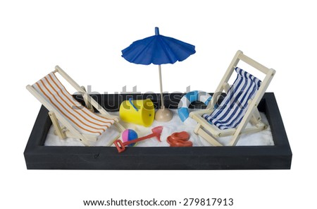 Folding beach chair with stripes with umbrella and shovel and pail for relaxing while on vacation - path included - stock photo