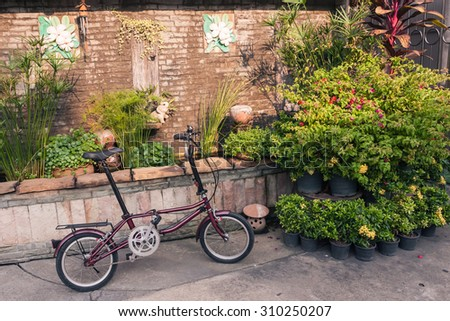 Folding Bike with old wall, Vintage color. - stock photo