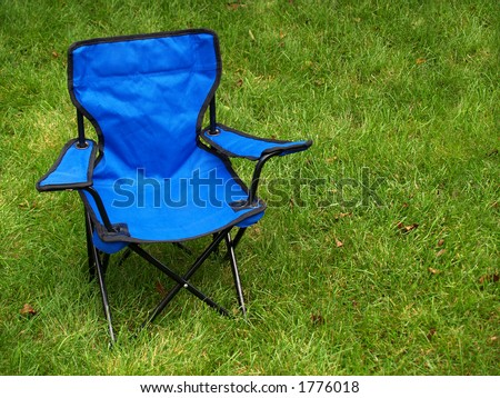folding blue camp chair on the lawn - stock photo