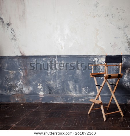 folding high chair at the wall, vintage background. square crop - stock photo
