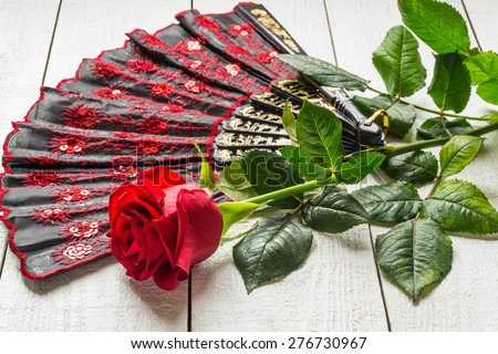 Folding patterned fan and red rose on a white wooden background. Selective focus - stock photo
