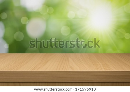 Foliage bokeh background with empty wooden table. Ready for product montage. Empty wooden table for product display montages - stock photo