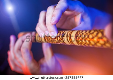 Folk musician in concert plays the melody on the Ethnic Flute - stock photo