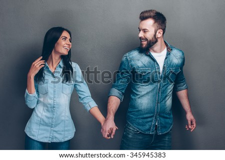 Follow me! Studio shot of beautiful young couple in jeans wear walking together and holding hands   - stock photo