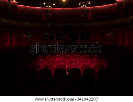 Follow spot on red velvet seat in a generic theater or movie cinema theater - stock photo