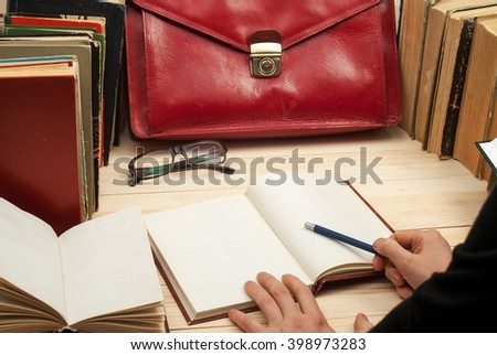 Follow the law. Professional lawyer sitting at the table and signing papers. On a wooden table books, documents, glasses, red briefcase. - stock photo