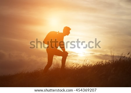 Follow your dreams, silhouette of man at sunset. Hiker with backpack walking in the field. Over sunset. Summer healthy active lifestyle. Single travel. - stock photo