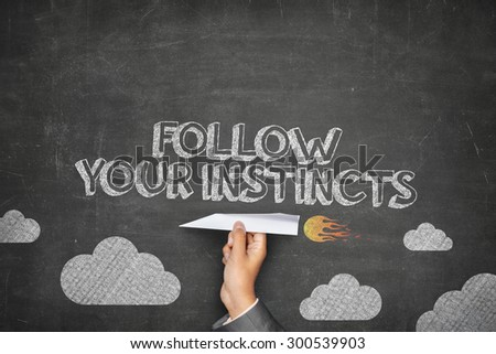 Follow your instincts concept on black blackboard with businessman hand holding paper plane - stock photo