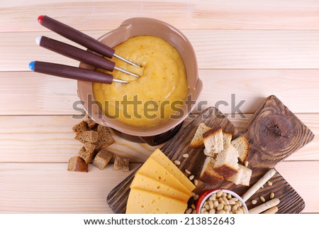 Fondue, biscuits, slices of cheese and rusks on cutting board on wooden background - stock photo