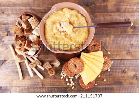 Fondue, slices of cheese and biscuits on wooden background - stock photo